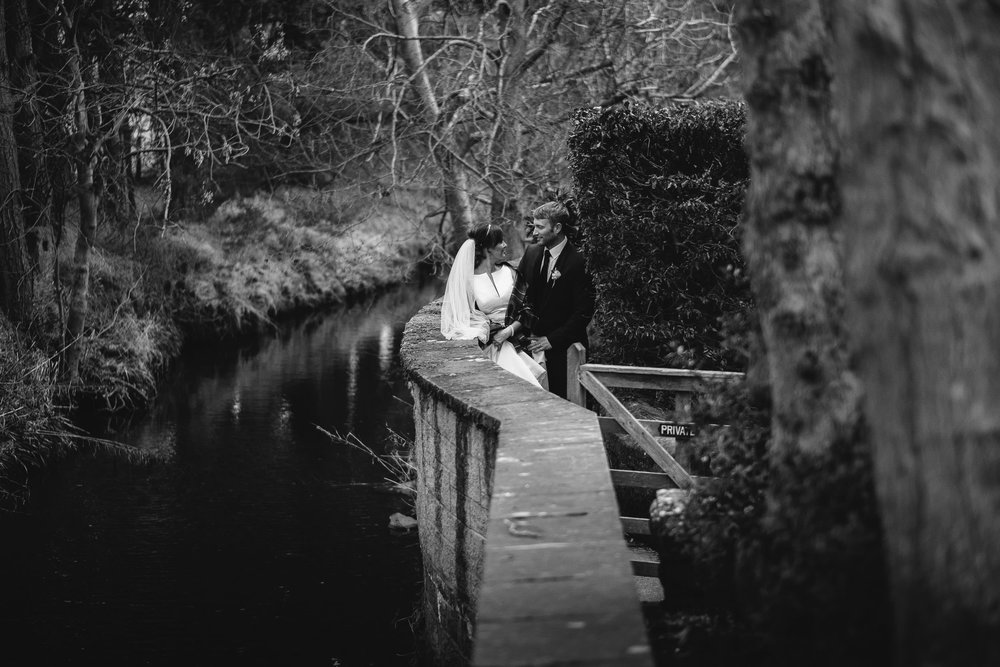 Black and white photo of bride and groom standing above stream in Otterburn, Northumberland