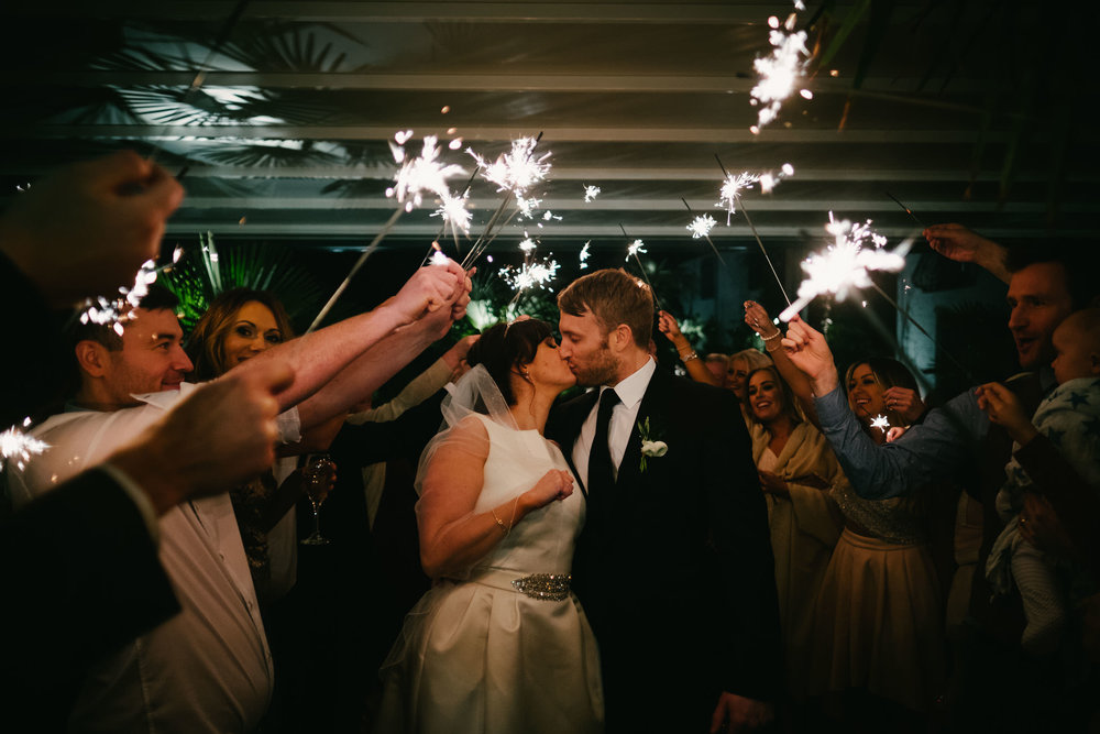 Bride and groom kiss under sparklers at Le Petit Château