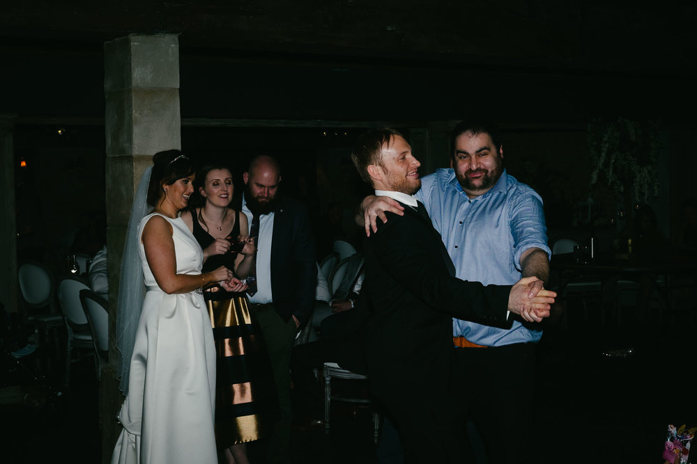 Groom and guest dance at wedding