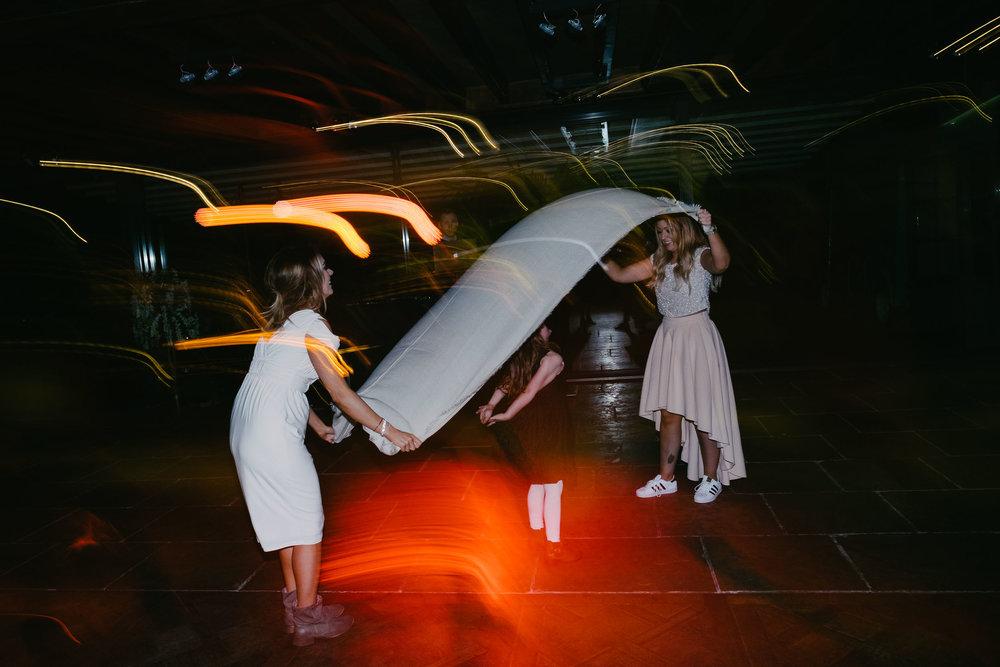Bridesmaids hold shrug as girl dances underneath it at wedding