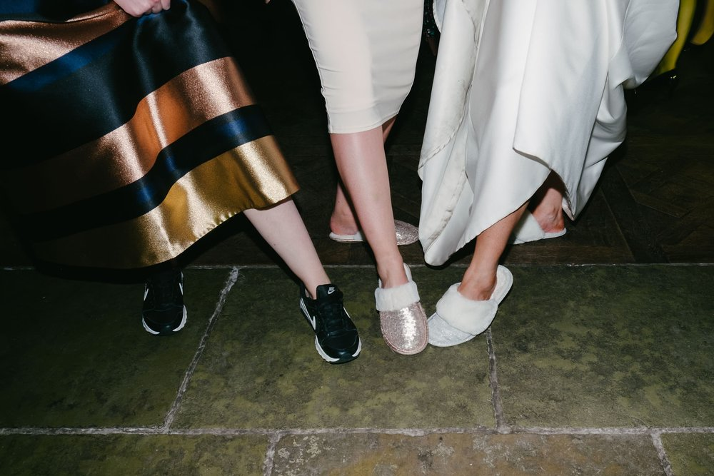 Funny photo of bride and guests comparing shoes at wedding