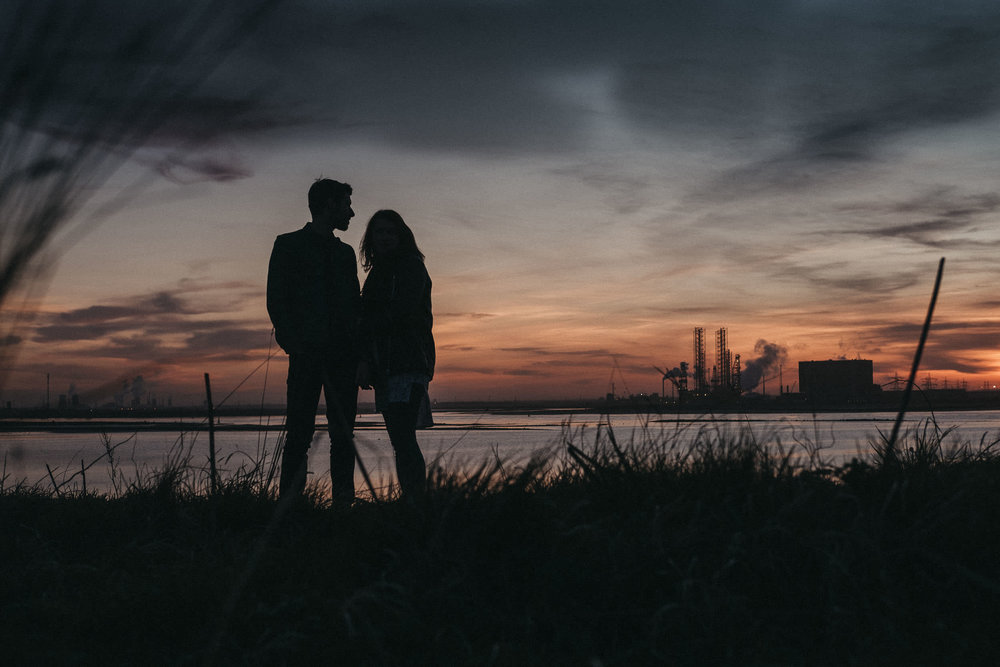 Silhouette of engaged couple at sunset with steelworks in the distance