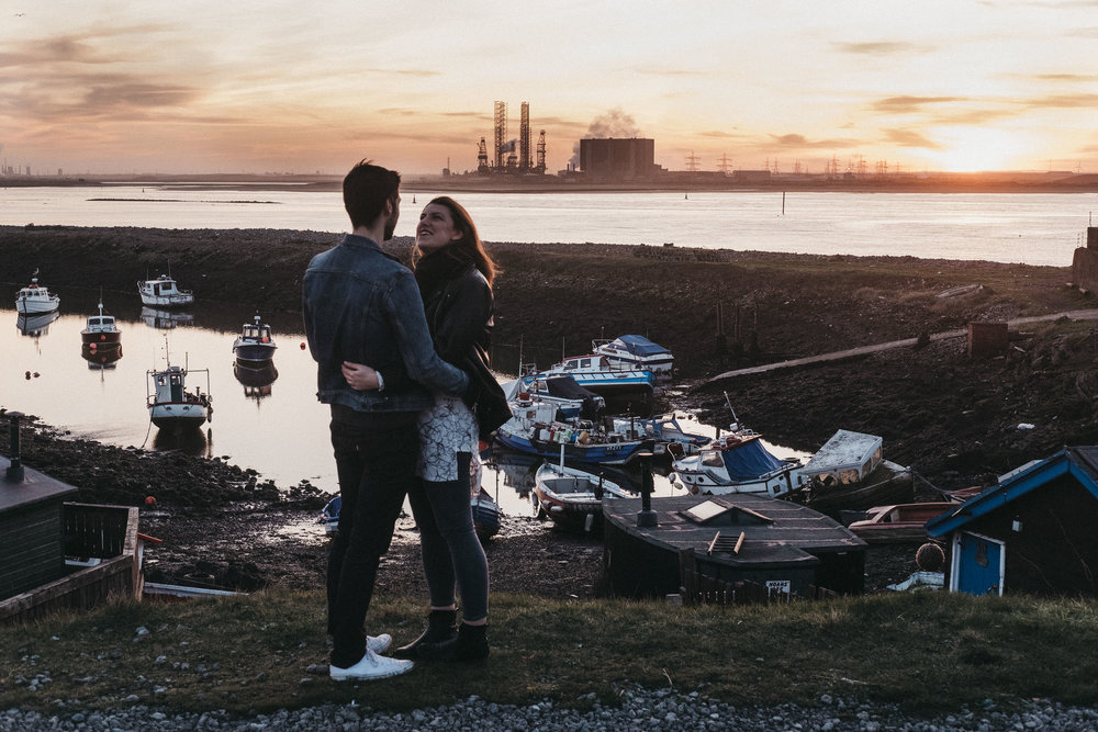 Couple cuddle with the boats at Paddy's Hole and steelworks behind them