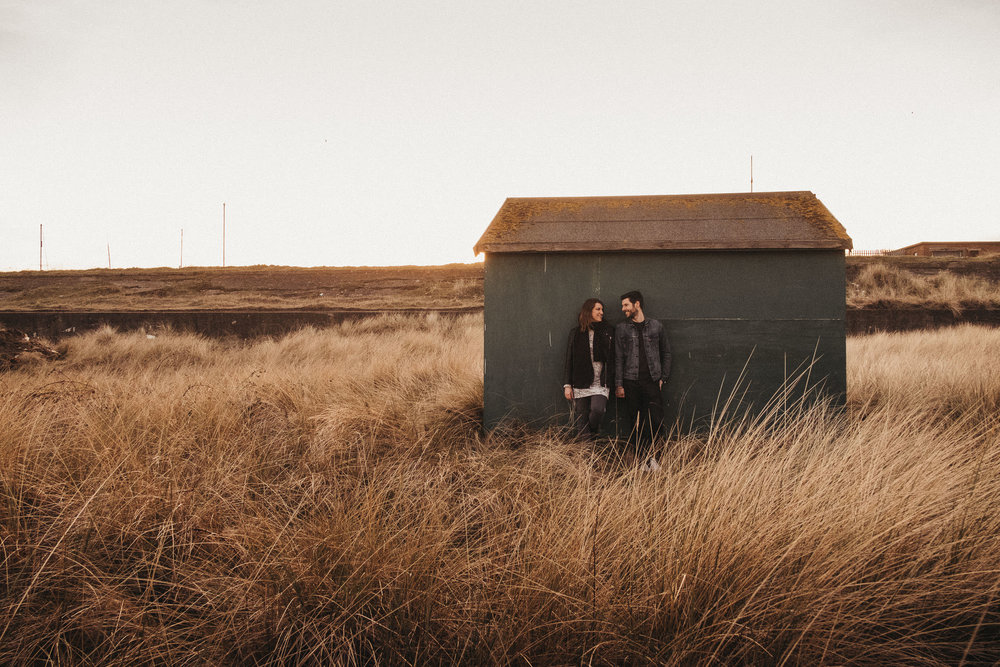 Couple lean against Fisherman's hut with long grass all around
