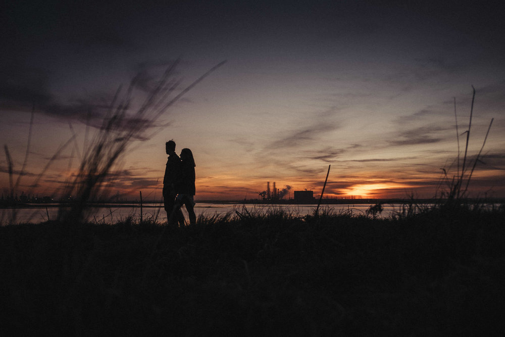 Silhouette of couple walking with long grass on the foreground and sunset in the background