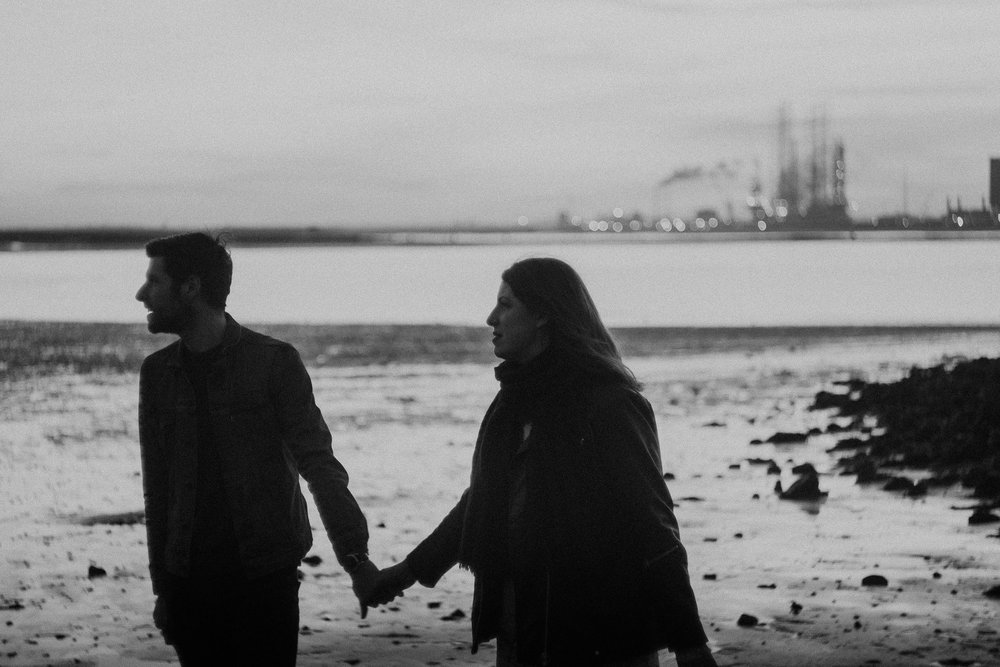 Black and white photo of couple holding hands on South Gare beach with steelworks behind