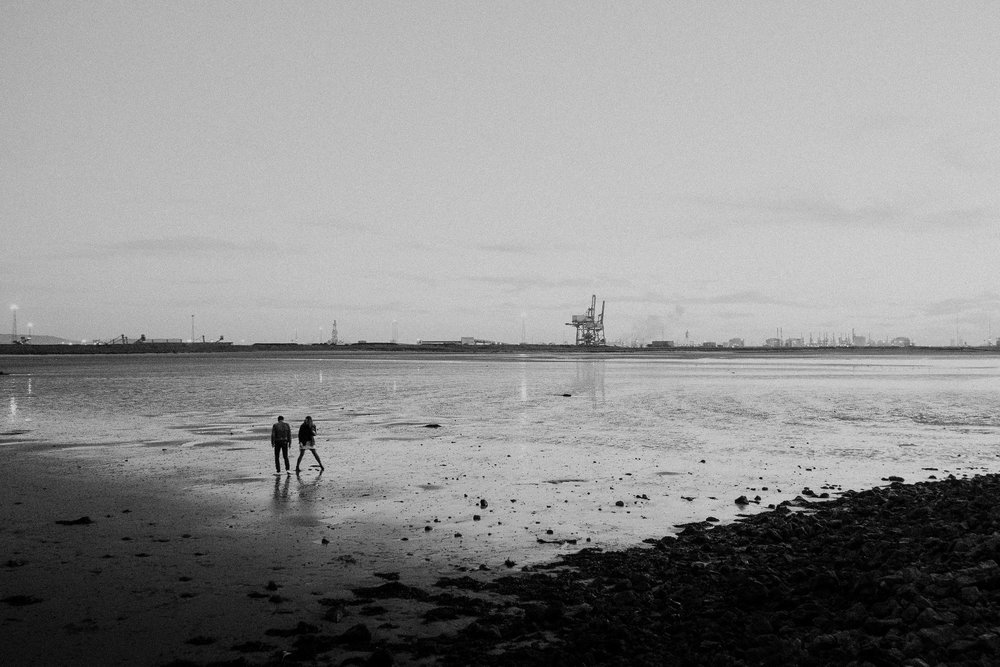 Black and white photo of couple on a beach at South Gare with signs of heavy industry behind