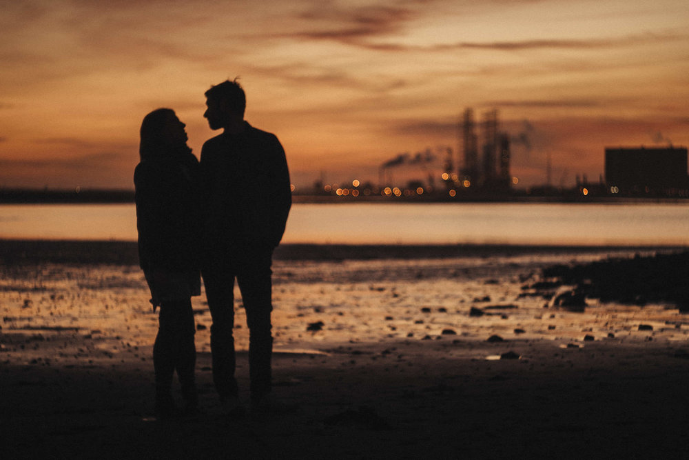 Silhouette of couple at South Gare at sunset with the steelworks in the distance