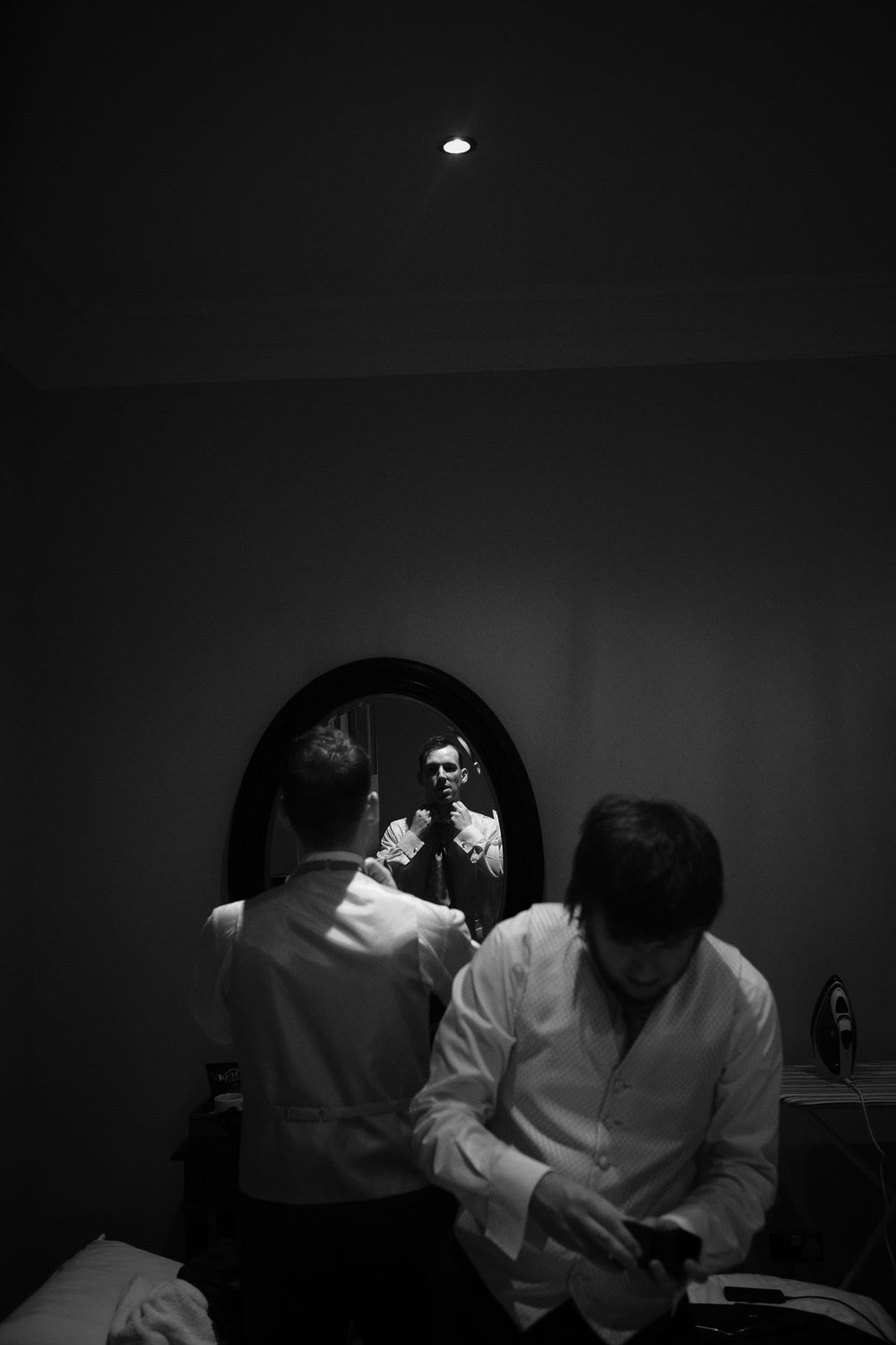 Moody black and white photo of groom getting ready reflected in mirror