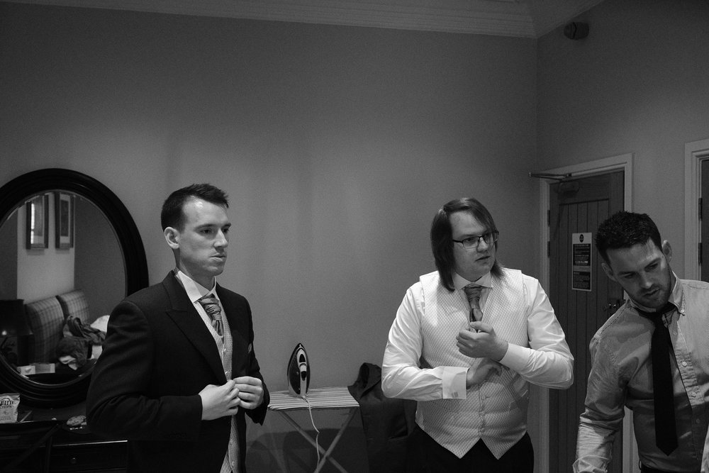 Black and white photo of groom and groomsmen getting ready