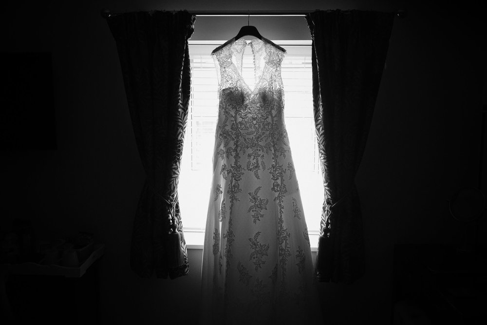 Black and white photo of dress hanging in window