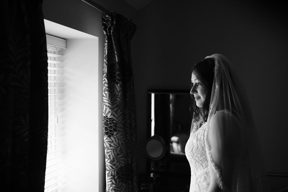 Black and white photo of bride looking out of window