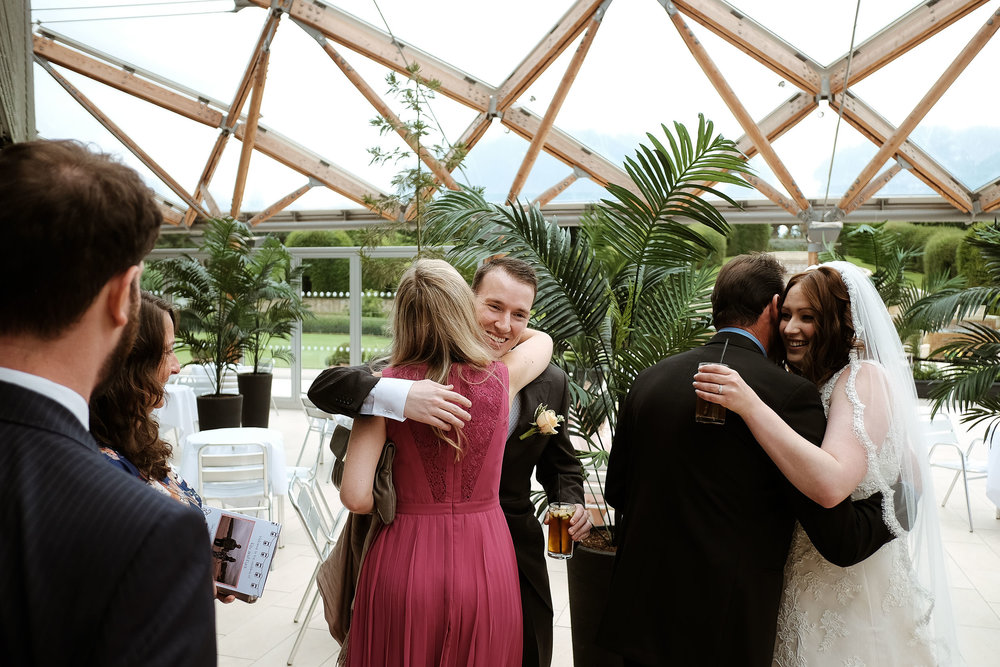 Bride and groom hug guests after wedding ceremony