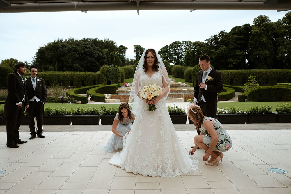 Bride having dress fixed by bridesmaids as groomsmen look on