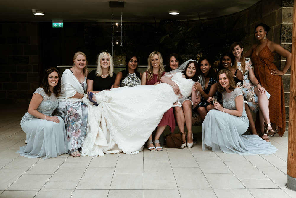 Bride being held up by bridesmaids
