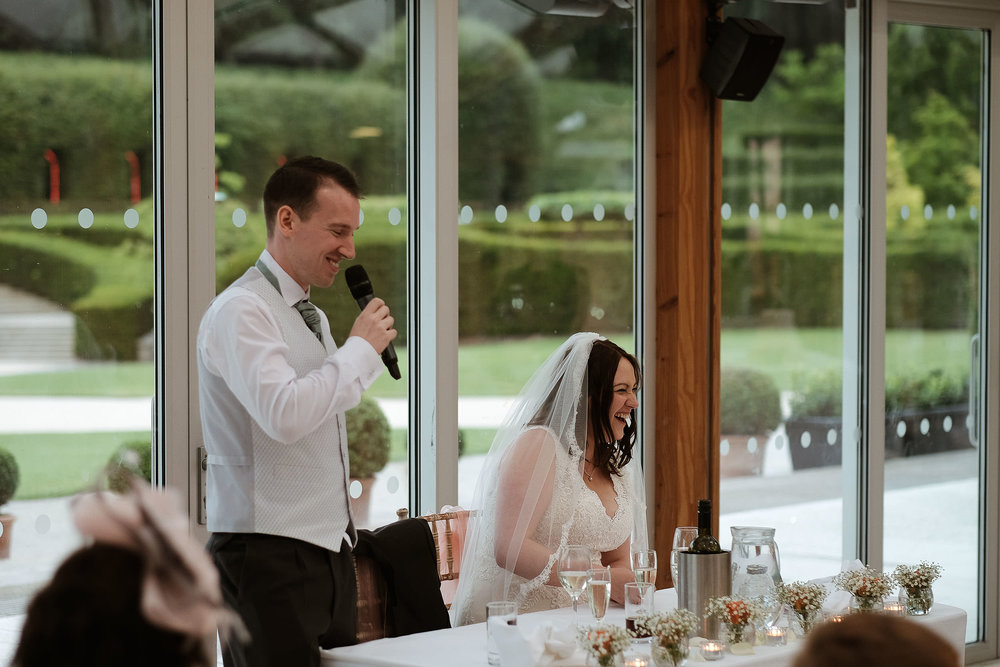 Groom giving wedding speech as bride laughs