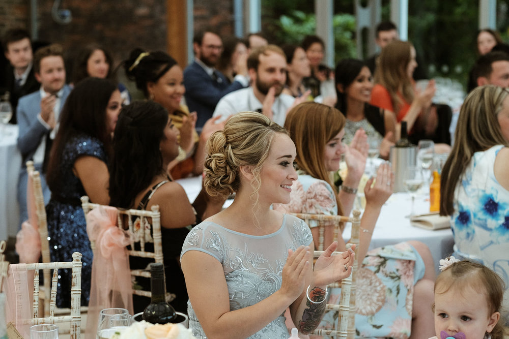 Guests clap at wedding speeches at the Alnwick Garden