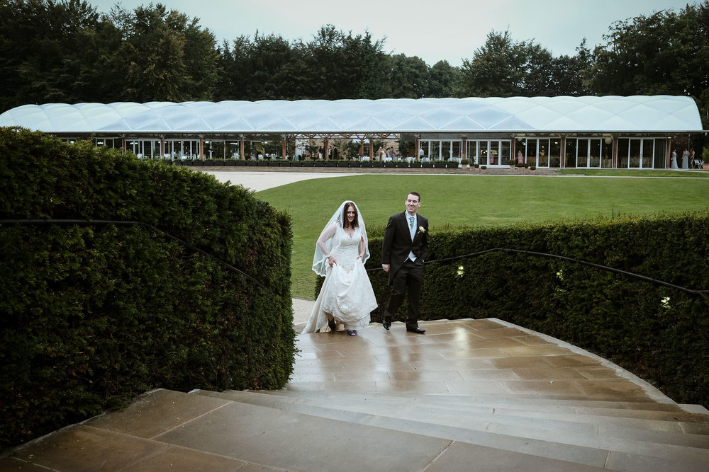 Bride and groom walking through the Alnwick Garden in the rain