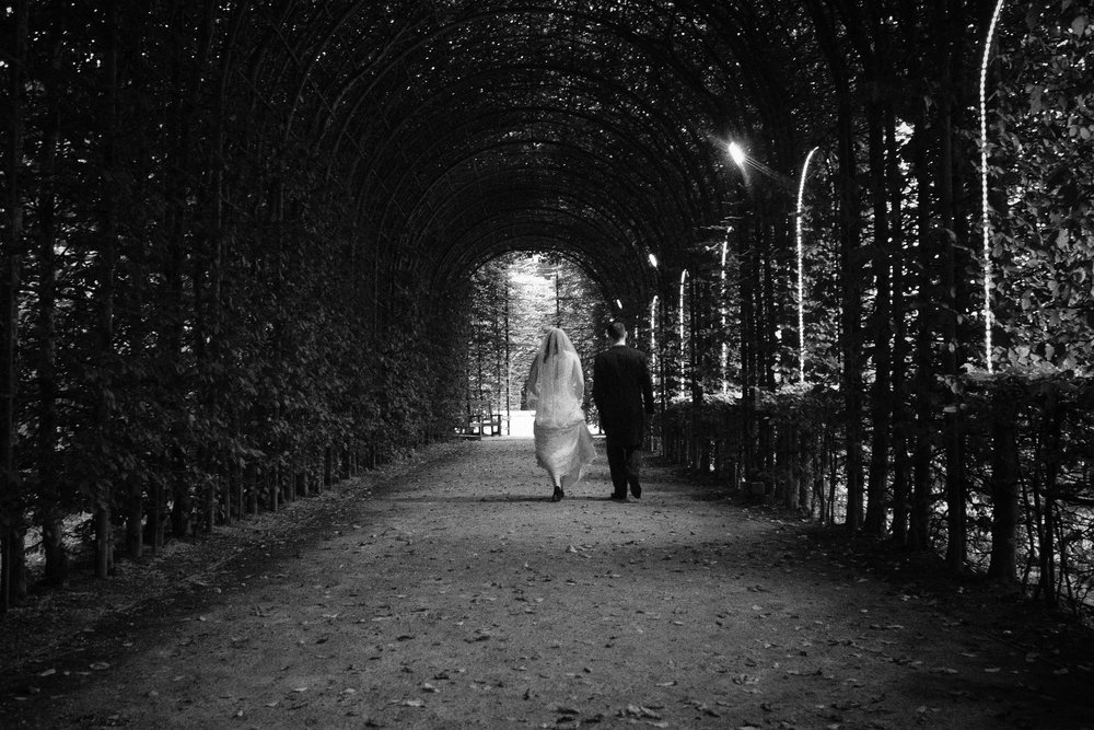Black and white photo of bride and groom walking under arches