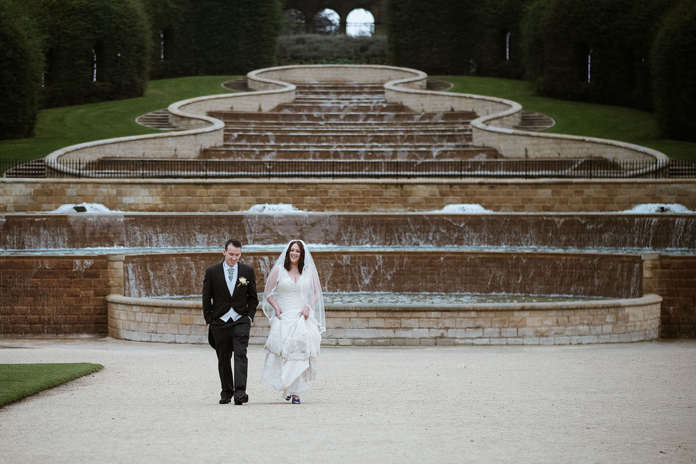 Bride and groom taking a stroll in front of the water fountains at the Alnwick Garden