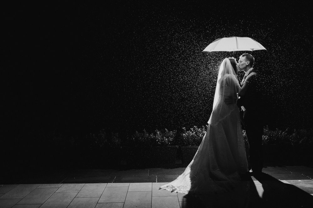 Black and white photo of bride and groom holding umbrella in the rain