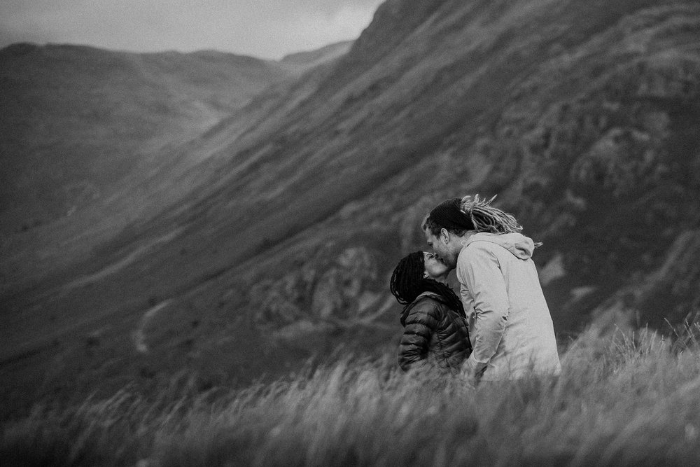 Black and white photo of engaged couple kissing on Lake District hillside