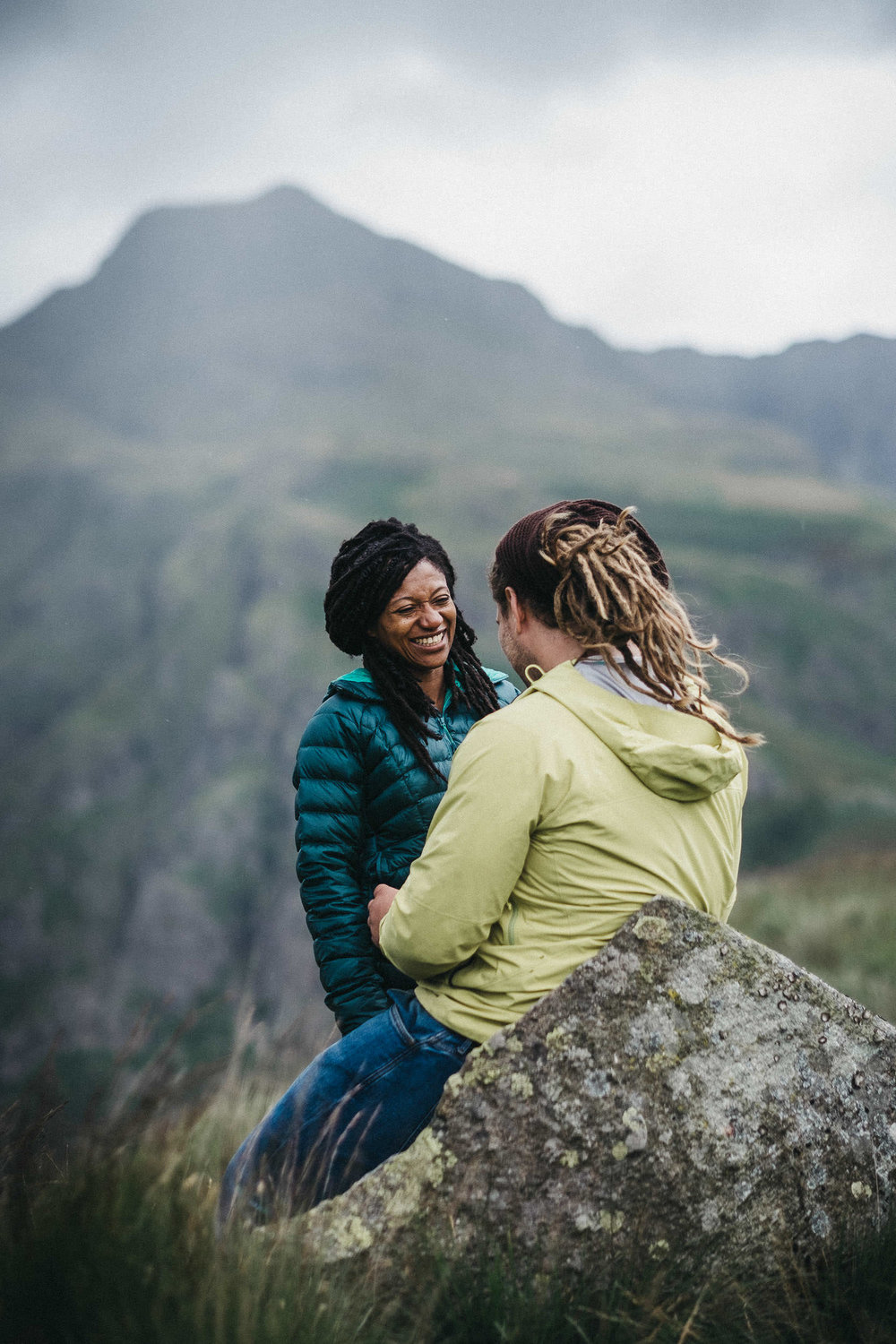 Couple with dreadlocks laughing while sat on a rock