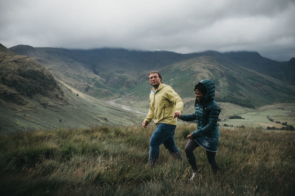Couple hold hands walking over hills in Buttermere Lake District