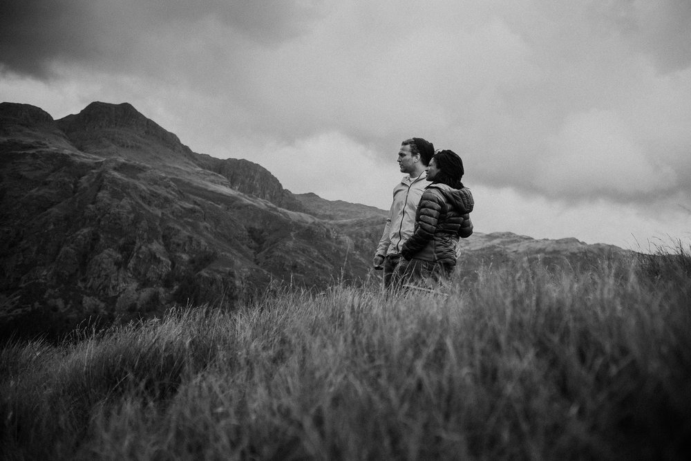 Black and white photo of couple cuddling while looking out over Lake District scenery