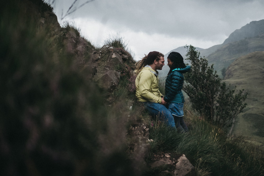 Engaged couple hold hands and look into each others eyes on the side of a mountain in the Lake District