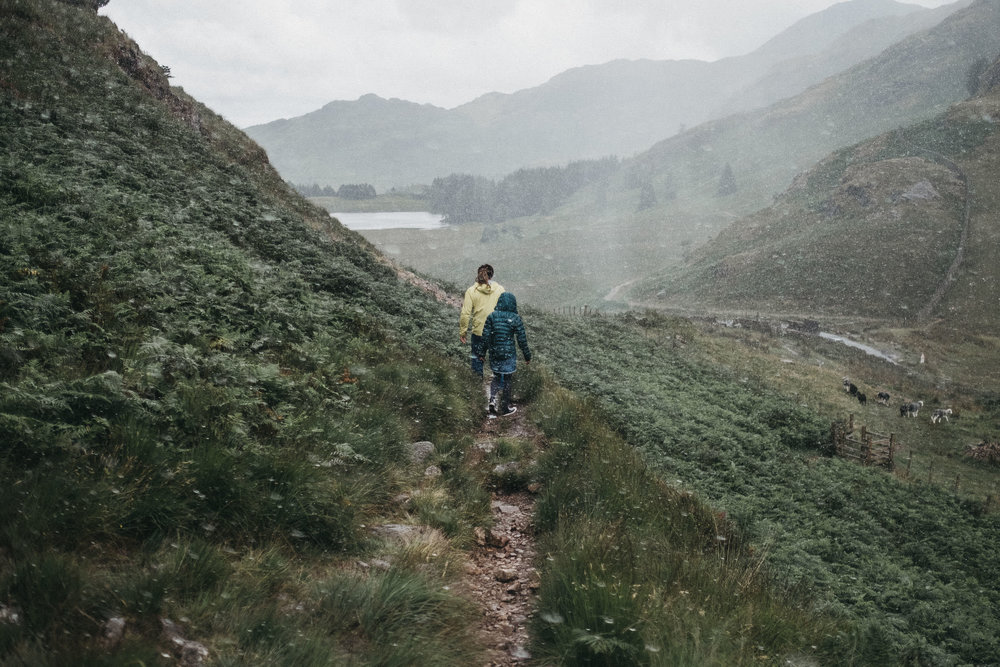 Pre-wedding photo of couple walking down a trail in the Lake District in the rain