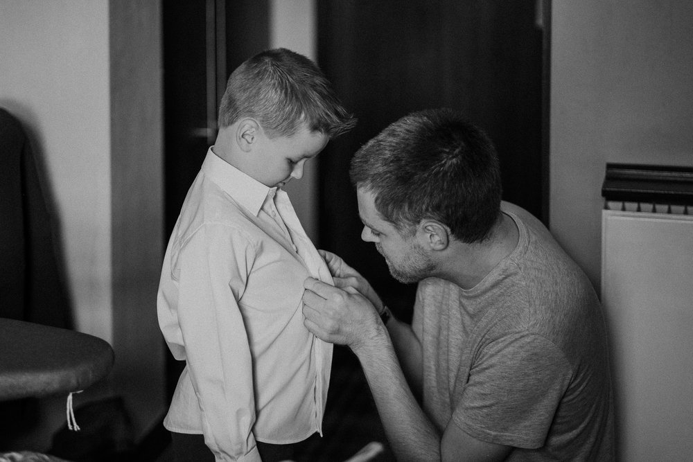 Black and white photo of groom getting page boy ready
