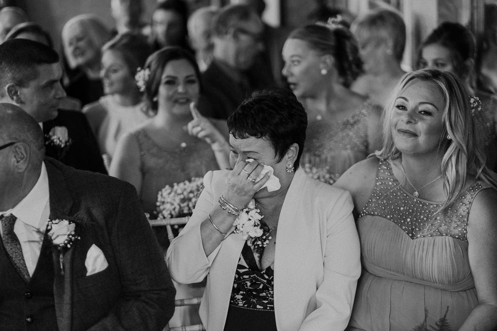 Black and white photo of the mother of the bride crying during the wedding ceremony
