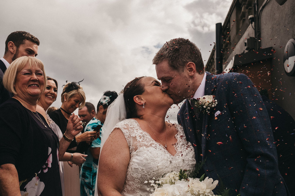 Bride and groom kissing while being showered in confetti