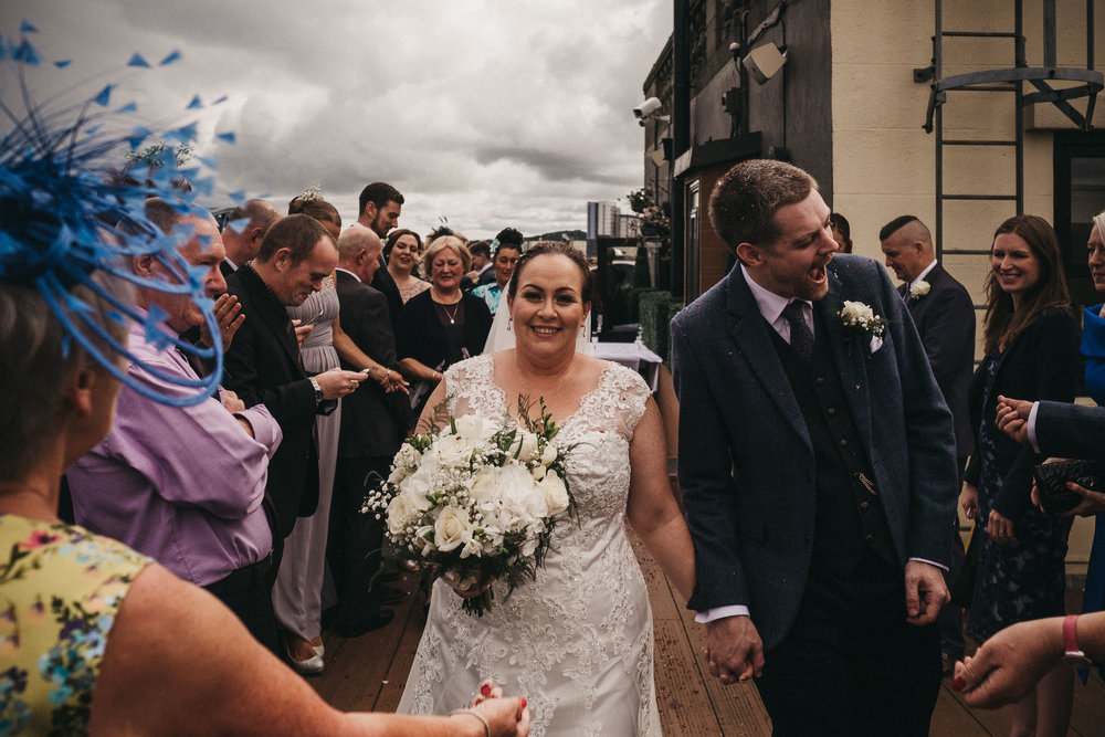 Groom pulling funny face as he walks past guests throwing confetti