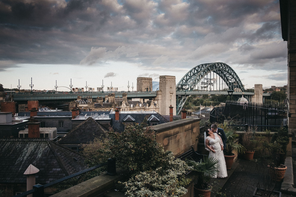Bride and groom kissing with Tyne Bridge in background