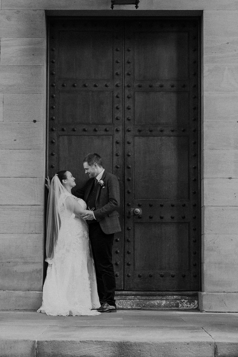 Black and white photo of bride and groom kissing in doorway of the Moot Hall