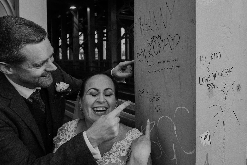 Black and white photo of bride and groom laughing at rude graffiti