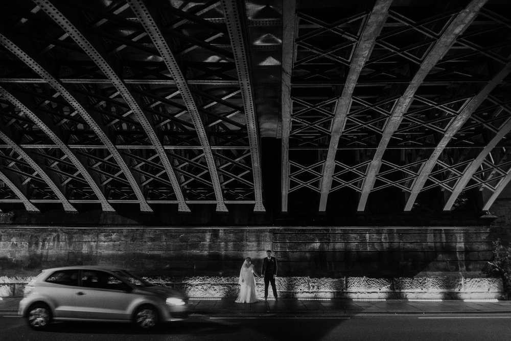 Black and white photo of bride and groom under steel bridge with car driving past