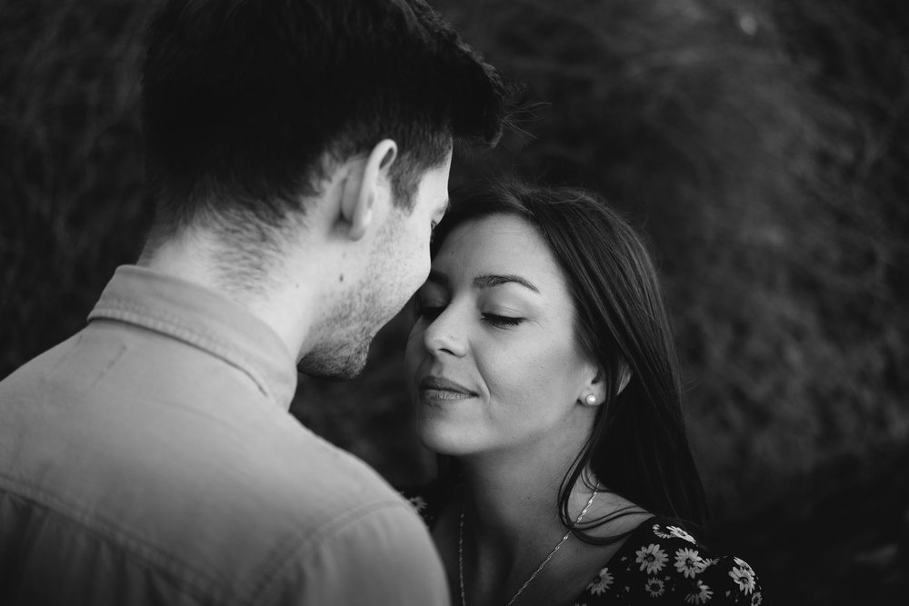 Black and white photo of engaged couple embracing
