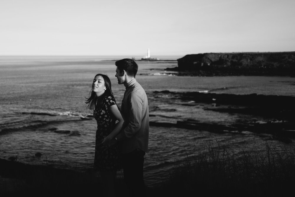 Black and white photo of couple having fun on clifftop at Seaton Sluice