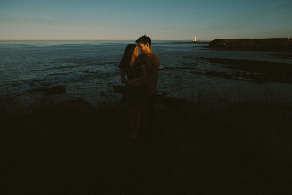 Couple in shaft of light on clifftop during pre-wedding shoot