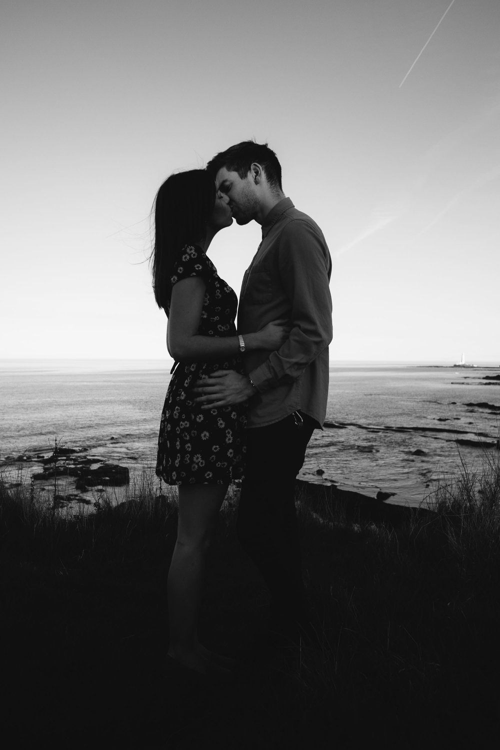 Black and white photo of couple kissing on clifftop during engagement session