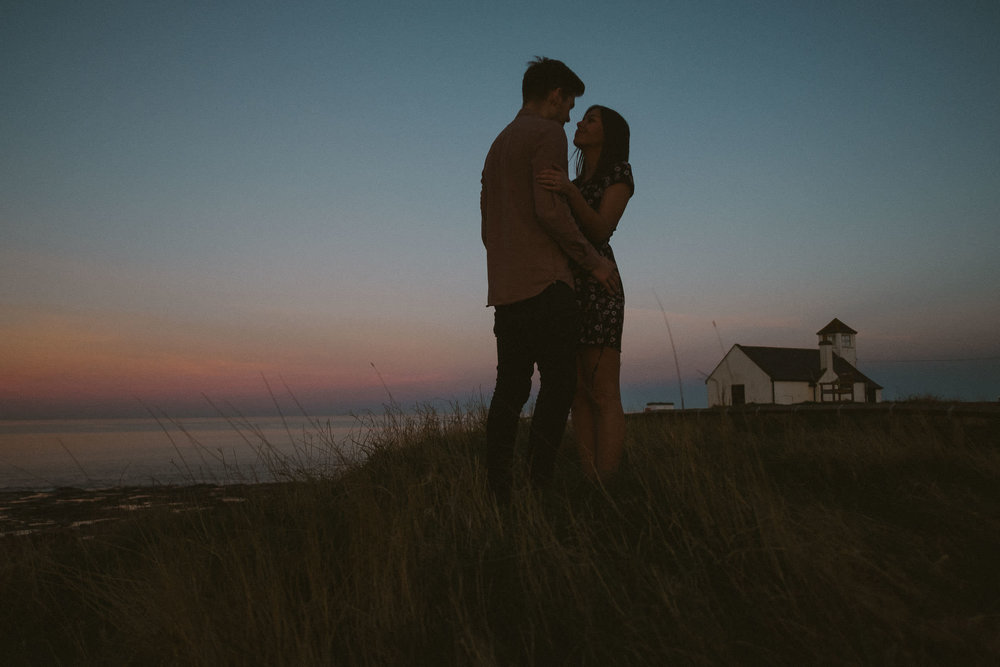Couple embracing on clifftop at sunset with cottage behind