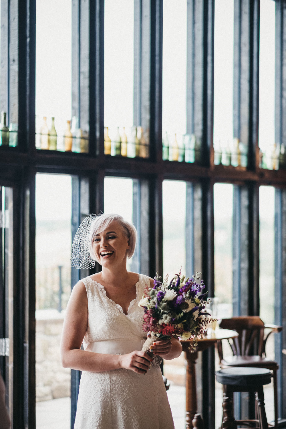 Bride laughing while holding bouquet at South Causey Inn