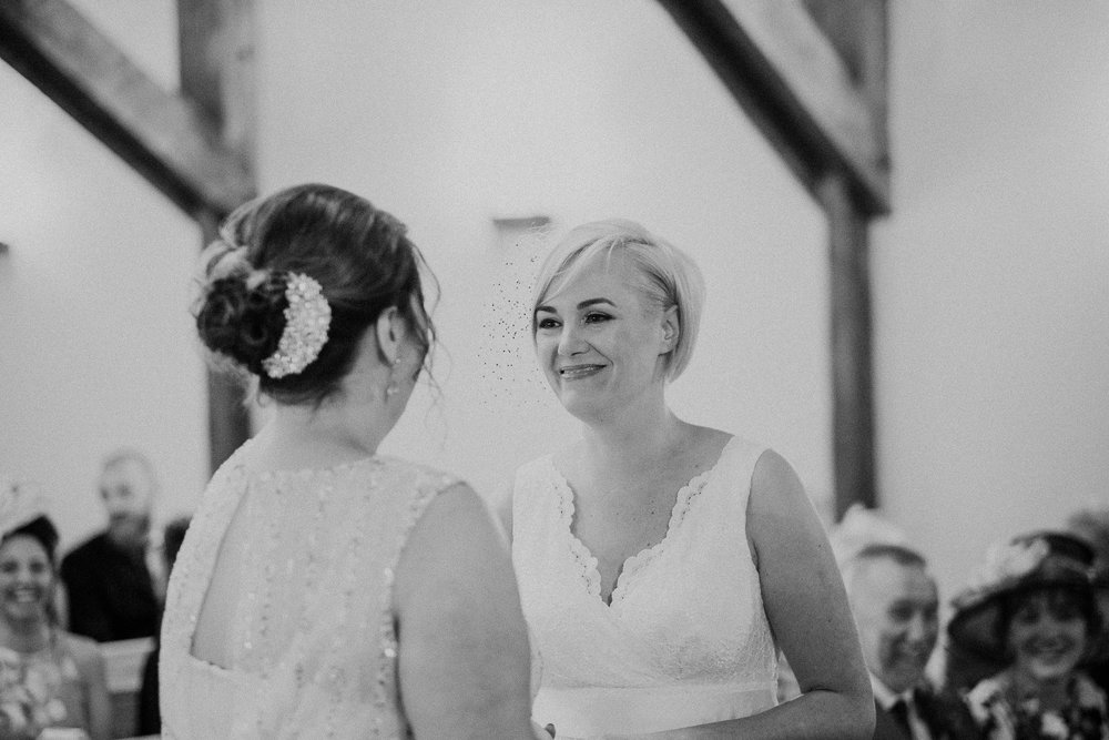 Black and white photo of brides smiling during wedding ceremony