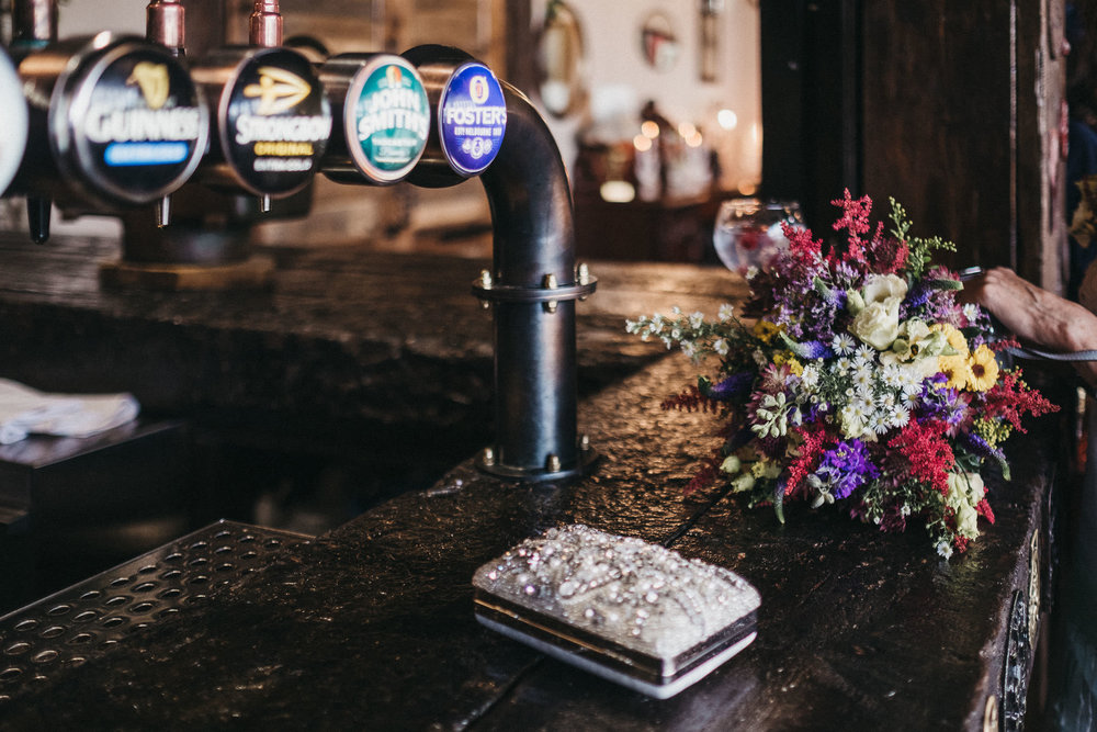 Wedding bouquet and purse on bar top