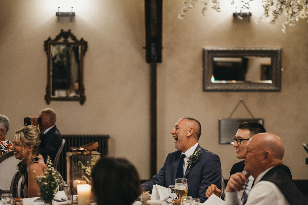 Father of bride laughs loudly during wedding speeches