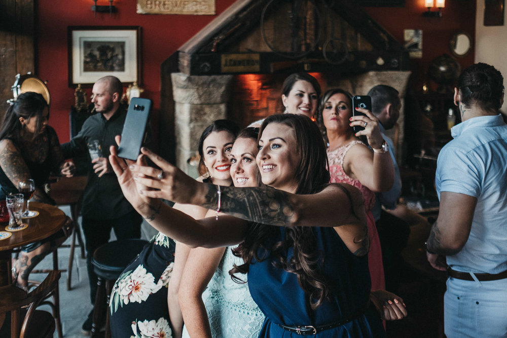 Two sets of guests take selfies at the same time