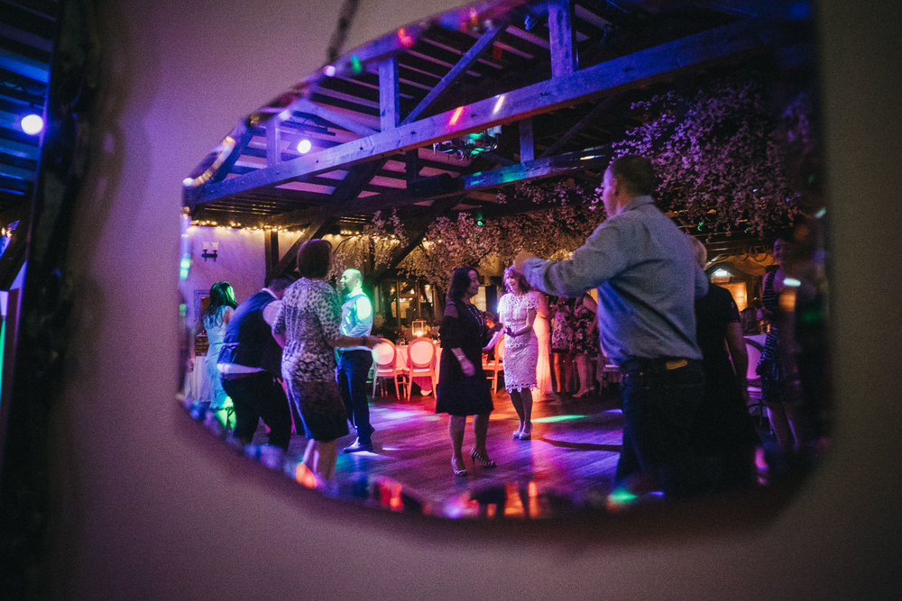 Colourful photo of wedding guests dancing reflected in mirror